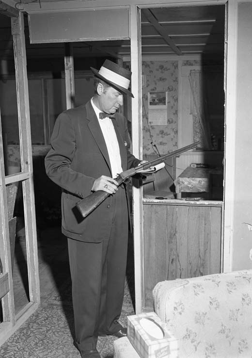 Boy Kills mother. Hom Det. H A Waldrip holds 22 rifle used by Jimmy Thomson to kill Hilda Thomson