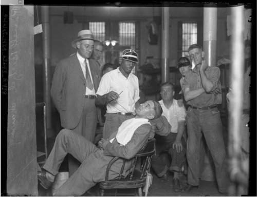 Convicted murderer, Russell Beitzel getting a shave in prison as other inmates look on, Los Angeles, Calif., 1928. [Photo courtesy of UCLA Digital Collection]