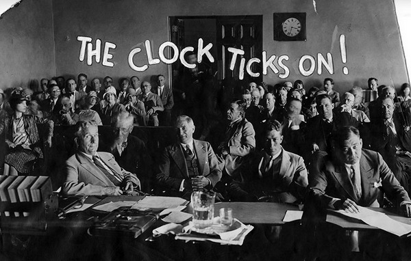 "Photograph caption dated September 10, 1929 reads, ""The clock ticks on, and the wheels of justice move on inexorably, slowly grinding out the fate of Mrs. Pantages. This courtroom scene shows the clock which ticks away the hours and will have ticked away before the case is done. It shows opposing attorneys who wage legal battles, witnesses ready to take the stand, and spectators. At left is Mrs. Pantages, waiting and looking at the clock."" [Photo courtesy of LAPL]"