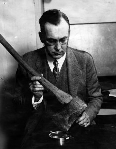 J. Clark Sellers, criminologist, examines an axe which Sanford Clark says Mrs. Louise Northcott used in Walter Collins' murder. Rex Welsh, police chemist, declares the axe is stained with human blood. It was found in a chicken coop on the ranch. Northcott said he killed the boys with a gun. [Photo courtesy LAPL]