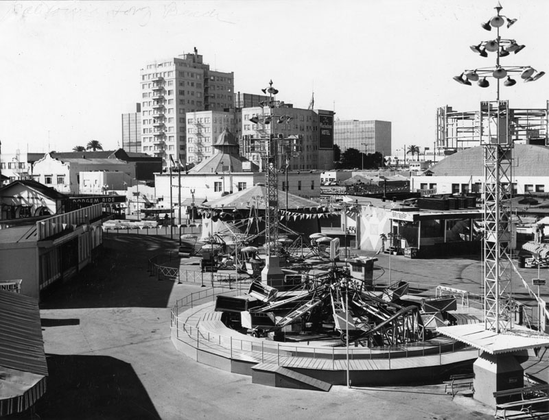 """Flood lights are off and crowds are absent in this view of The Pike in Long Beach. In the background is the Blackstone Hotel and the Penny Arcade. A banner welcoming KWKW radio station is on a building, background, right, behind the """"Batter Up"""" concession. Amusement rides are in the center.  [Photo courtesy LAPL.]"""